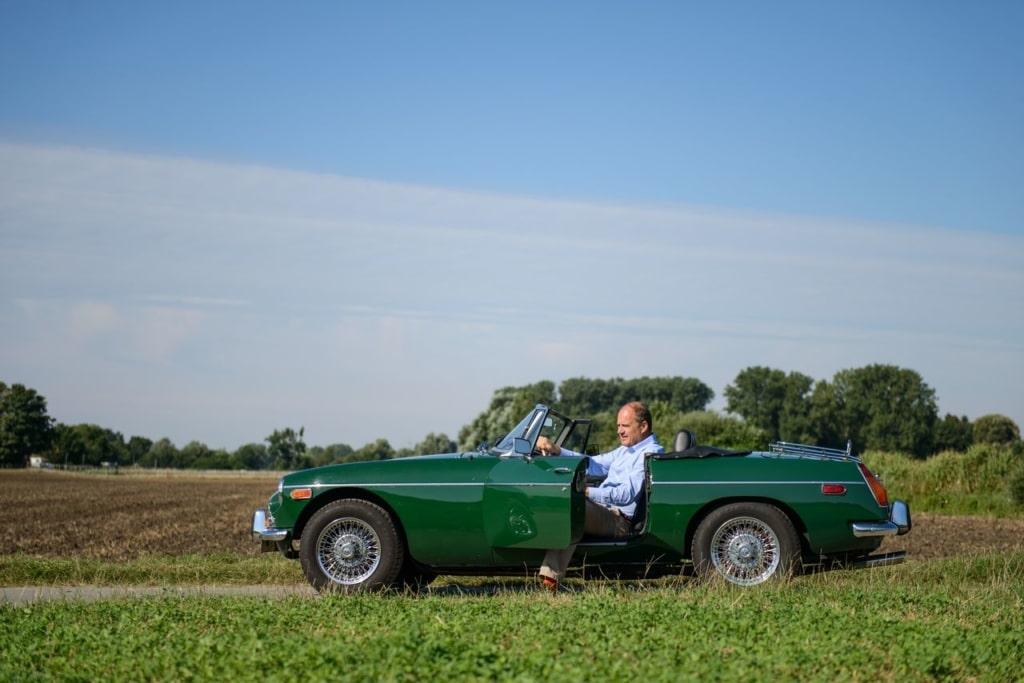 Steuerberater Michael Schiele sitzt in seinem Oldtimer mit geöffneter Tür auf einem Feldweg